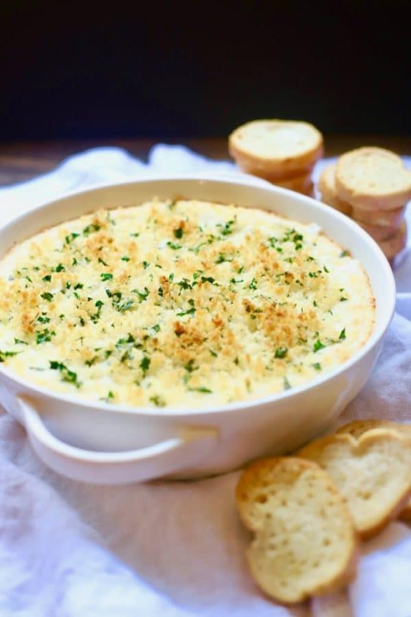 Hot and Cheesy Baked Shrimp Scampi Dip with toasted bread rounds ready for serving