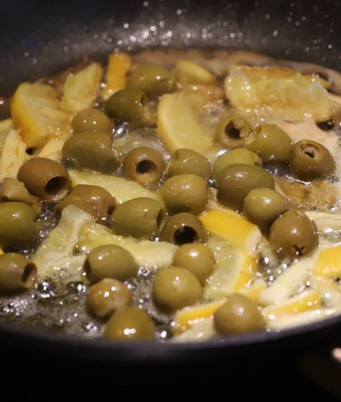 Cooking olives and lemon slices in a large skillet for Skillet Chicken with Lemon and Olives