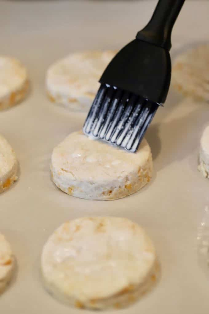 Brushing cream on raw biscuit dough to help them brown for Easy Southern Cheddar Biscuits