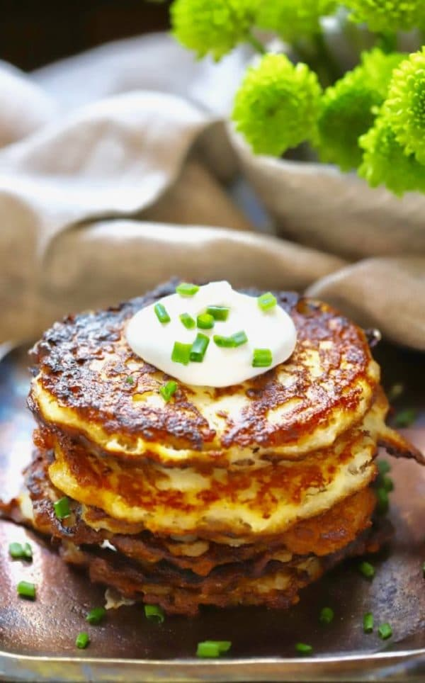 Traditional Irish Potato Boxty topped with sour cream and chives with green flowers in the background