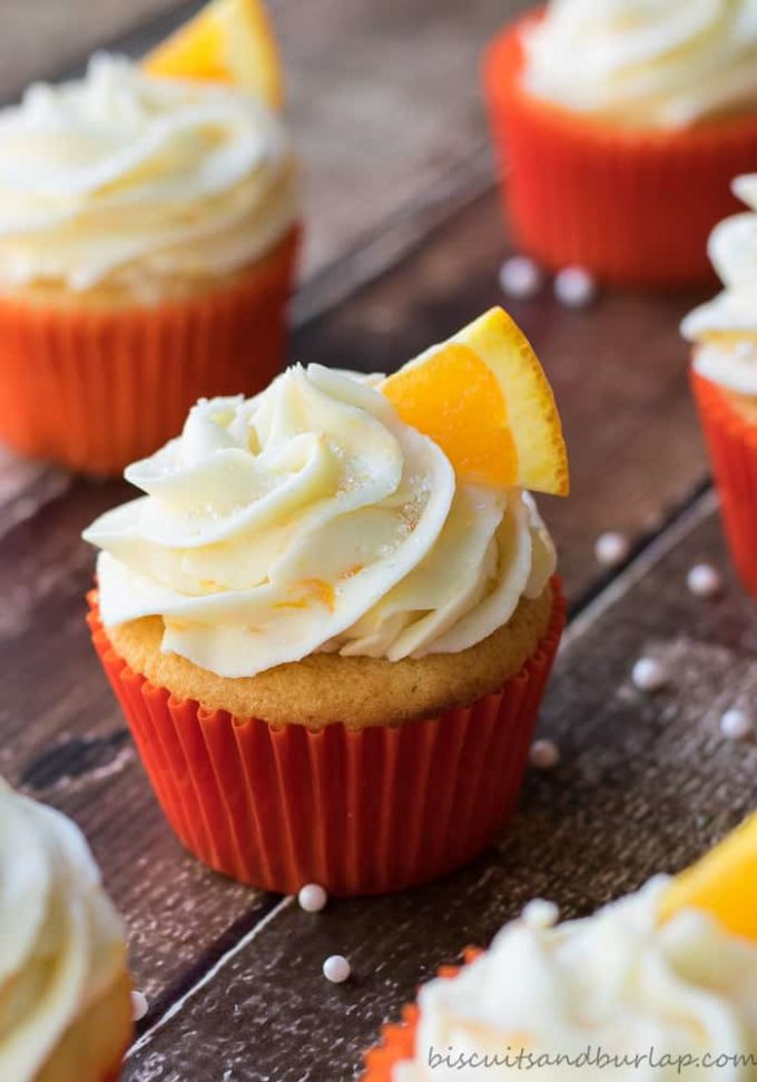Several orange cupcakes with orange cream cheese icing garnished with an orange slice