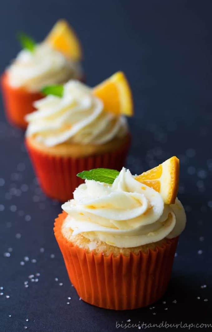 A row of orange cupcakes with orange cream cheese icing garnished with orange slices and mint leaves