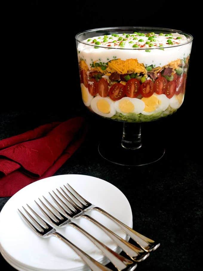 Classic Southern Seven Layer Salad with plates and forks ready to serve