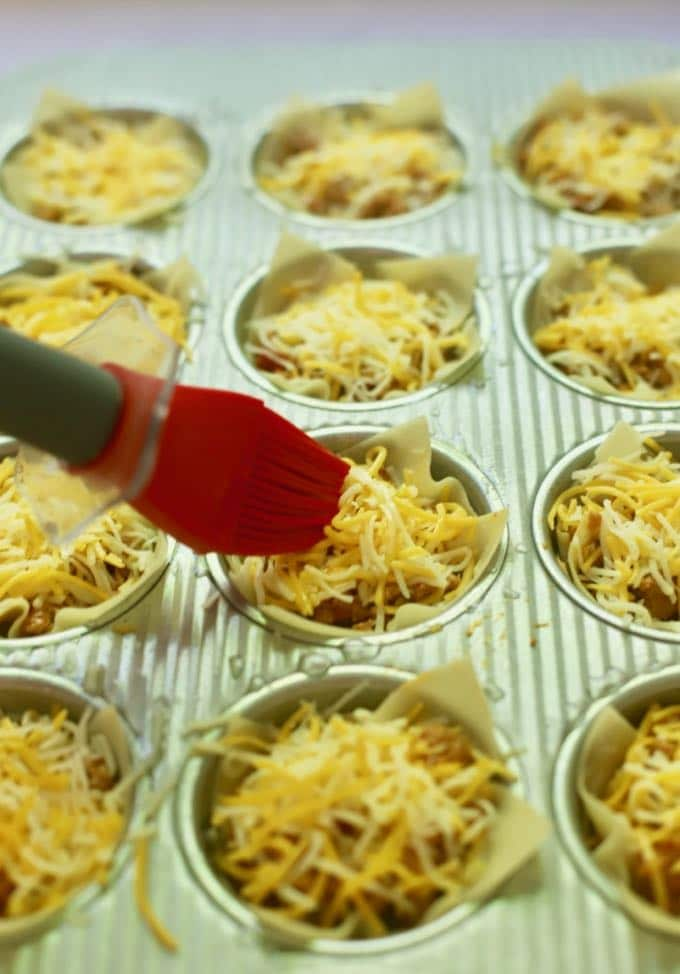 Using a pastry brush to brush on vegetable oil to wonton wrappers in a muffin pan for Easy Crunchy Taco Cups