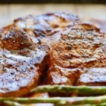 Easy Grilled Pork Chops and Marinade with pork chops right off of the grill on a wooden cutting board resting