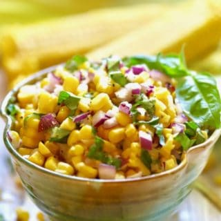 Easy Southern Corn Salad in a green pottery bowl with fresh corn cobs in the background