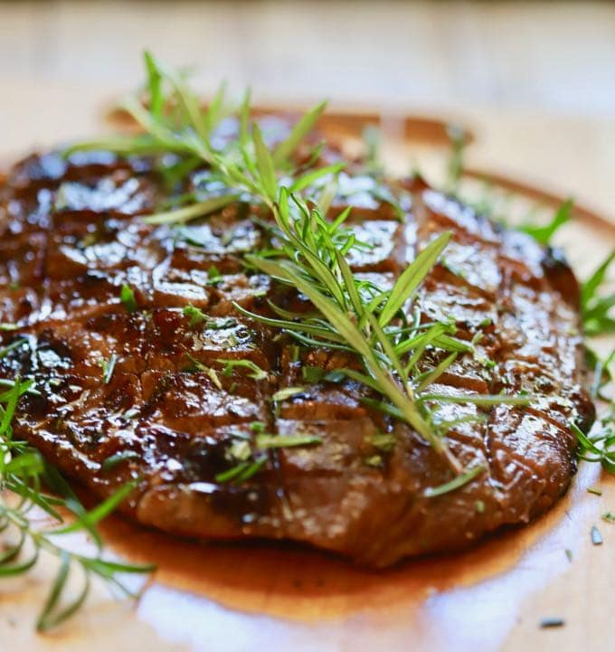 Ultimate Grilled Flank Steak resting on a cutting board garnished with fresh rosemary