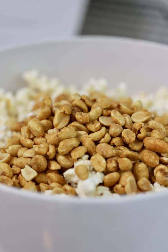 A bowl of popcorn topped with peanuts for Caramel Corn with Dark Chocolate Drizzle