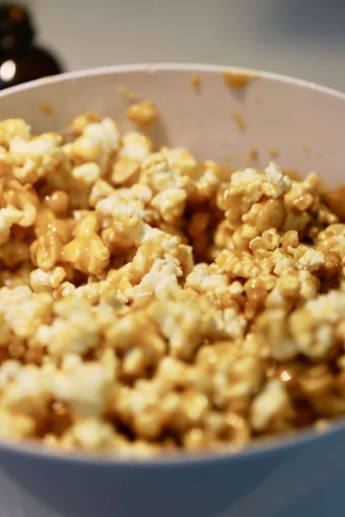 Popcorn and peanuts in a large white bowl mixed with caramel sauce for Caramel Corn with Dark Chocolate Drizzle