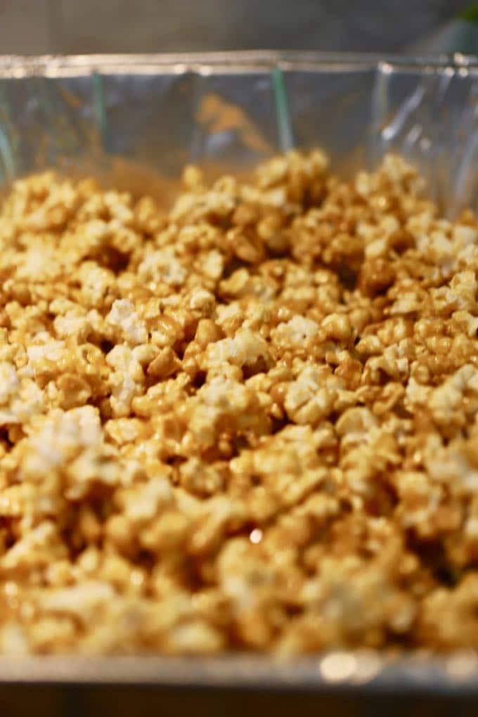 Caramel corn in a large disposable aluminum pan ready to bake for Caramel Corn with Dark Chocolate Drizzle