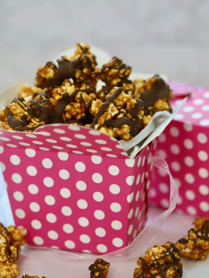 A pink and white polka dot box full of Caramel Corn with Dark Chocolate Drizzle
