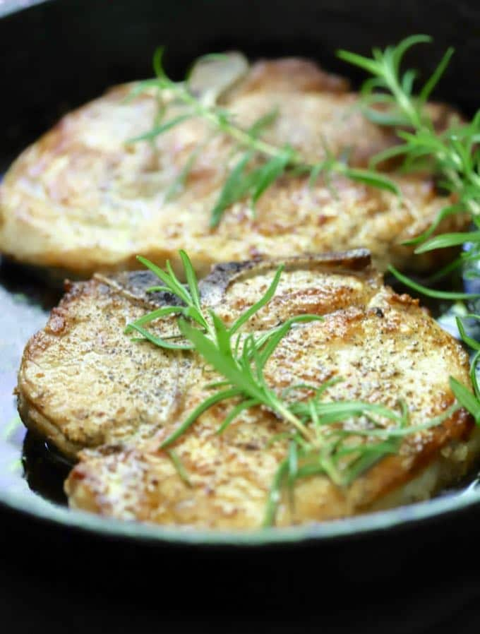 A sprig of rosemary garnishes pork chops in a cast iron pan for Easy Baked Pork Chops with Rosemary