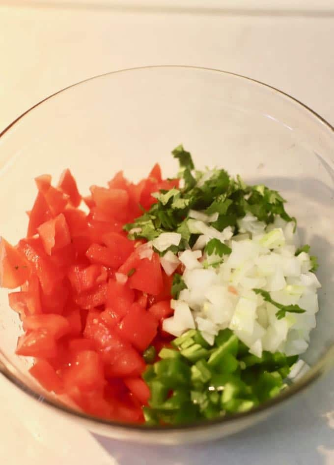 Chopped tomatoes, cilantro, onion, and jalapeños in a clear glass bowl.