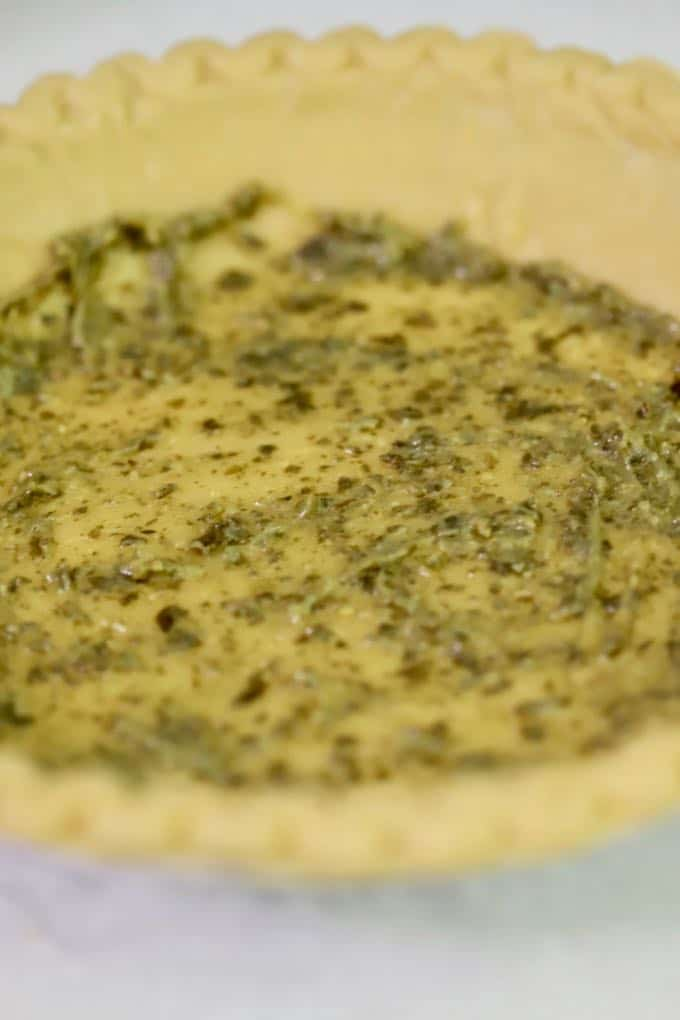 Spreading pesto over an unbaked pie shell for Roasted Tomato Quiche with Goat Cheese