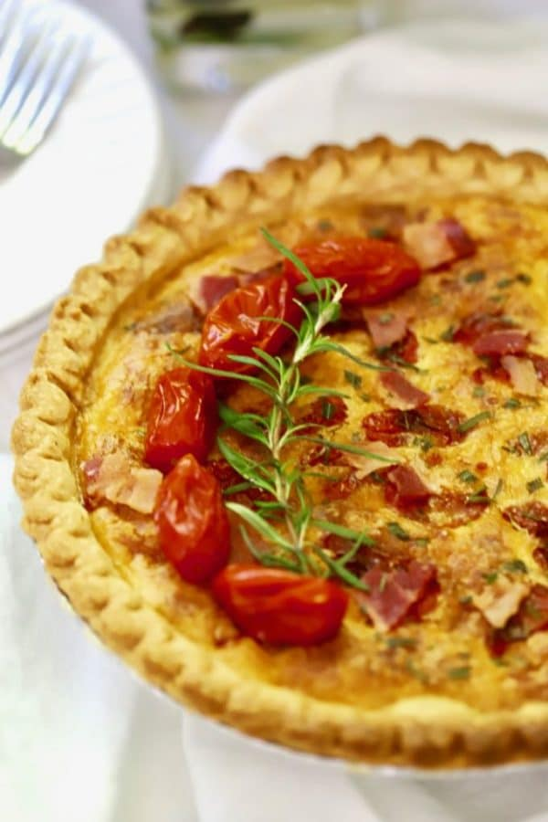 Roasted Tomato Quiche with Goat Cheese garnished with cherry tomatoes and fresh rosemary