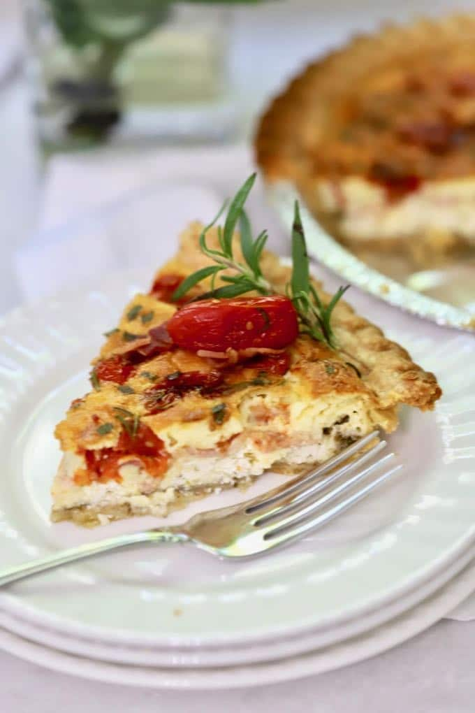 A slice of Roasted Tomato Quiche with Goat Cheese garnished with a roasted tomato and sprig of fresh rosemary