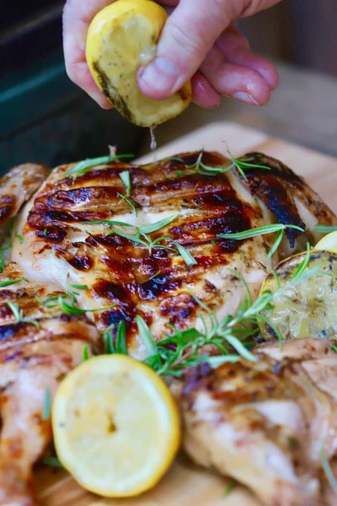 Squeezing lemon juice over Simple Lemon Grilled Chicken to serve