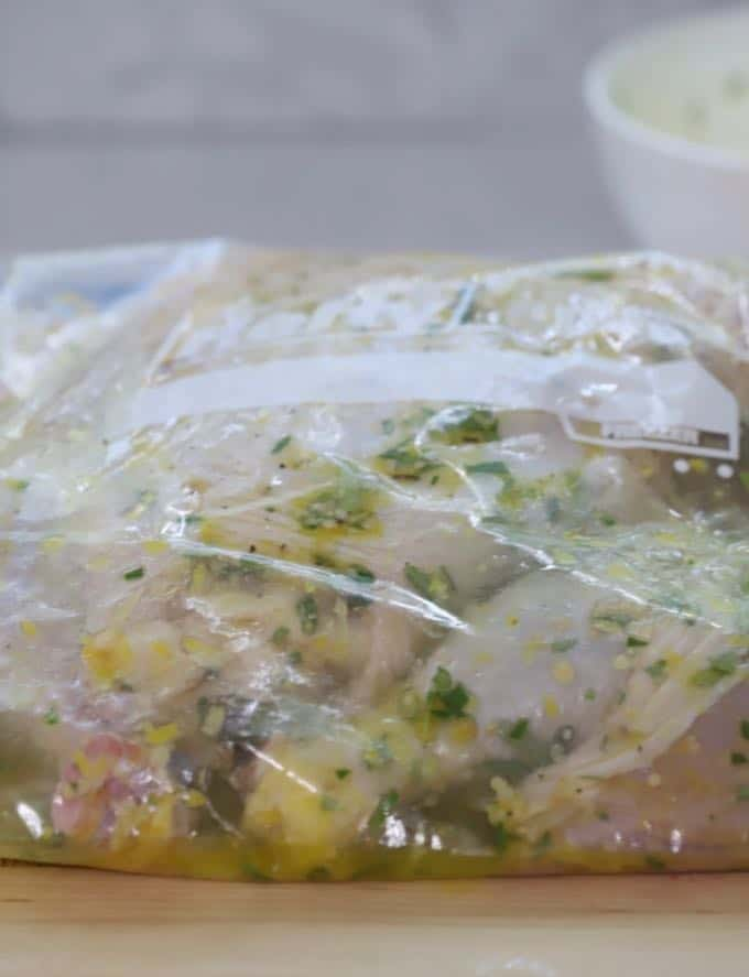 Simple Lemon Grilled Chicken marinating in a bag with an olive oil, lemon juice, garlic, and rosemary marinade