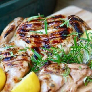 Simple Lemon Grilled Chicken right off the grill, on a cutting board, garnished with lemons and rosemary
