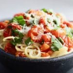 Spaghetti with Fresh Cherry Tomato Sauce in a large black pottery bowl, garnished with basil and topped with parmesan cheese