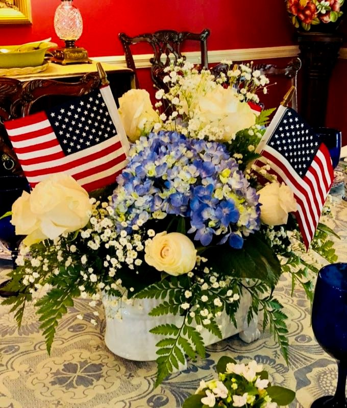 A patriotic 4th of July flower arrangement with American flags