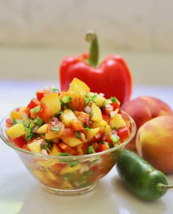 A clear glass bowl of Easy Southern Fresh Peach Salsa with a red bell pepper, peaches and a jalapeno pepper next to it.