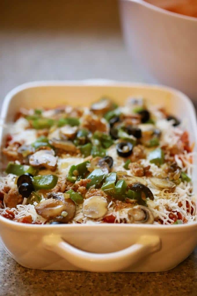 Easy Supreme Pizza Casserole in a white baking dish and ready for the oven.