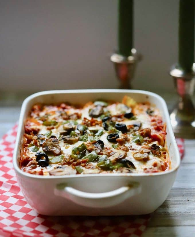 Easy Supreme Pizza Casserole in a white baking dish on a table ready to serve.