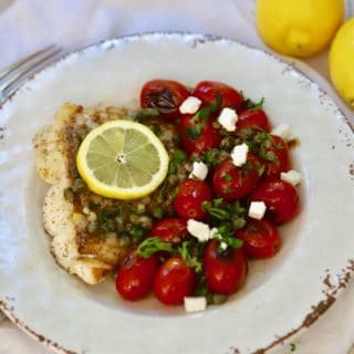 Pan Fried Fish with Blistered Tomatoes on a white plate garnished with crumbled feta cheese