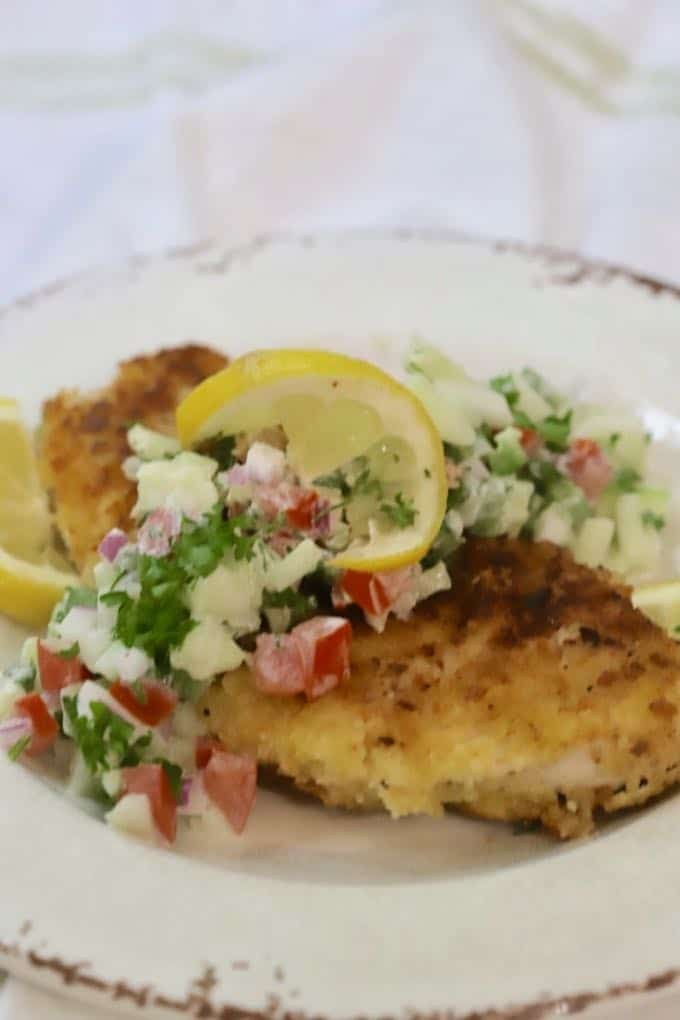 Parmesan Chicken topped with Cucumber Salsa and garnished with a slice of lemon