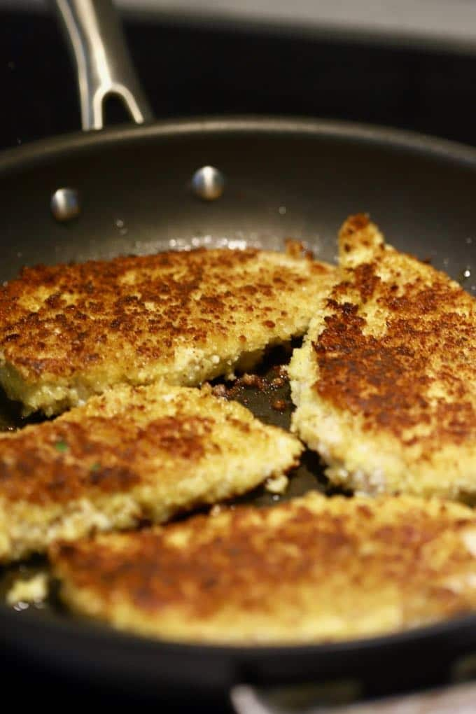 Parmesan and panko coated chicken breasts cooking in a skillet to make Parmesan Chicken with Cucumber Salsa