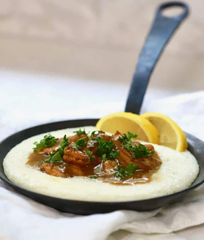 BBQ Shrimp and Cheese Grits in a black cast iron pan garnished with parsley and lemon slices