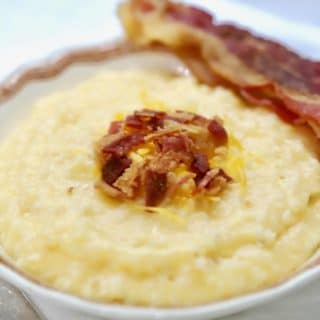 Southern Crockpot Easy Cheesy Grits topped with bacon in a bowl