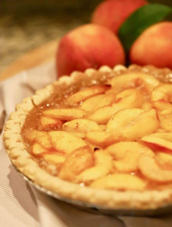 Southern Style Easy Fresh Peach Pie in a pie plate with fresh peaches behind it.