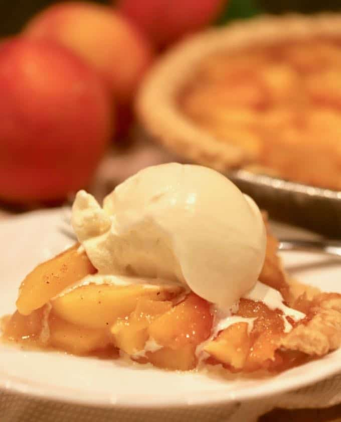 A scoop of vanilla ice cream tops a piece of Southern Style Easy Fresh Peach Pie