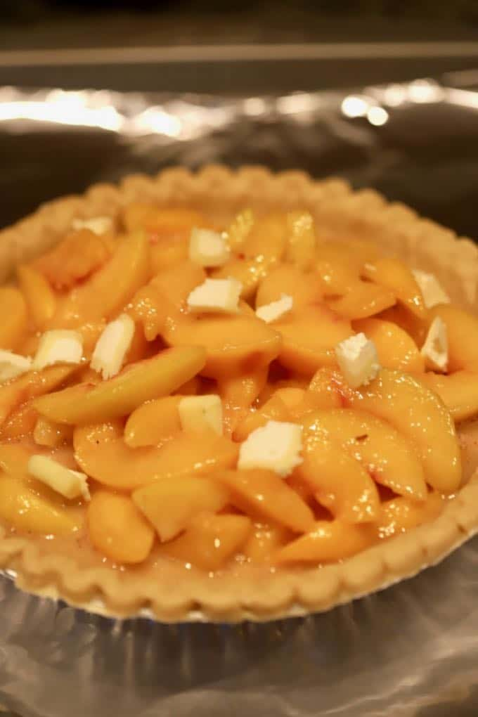 Small pats of butter cover and unbaked Southern Style Easy Fresh Peach Pie