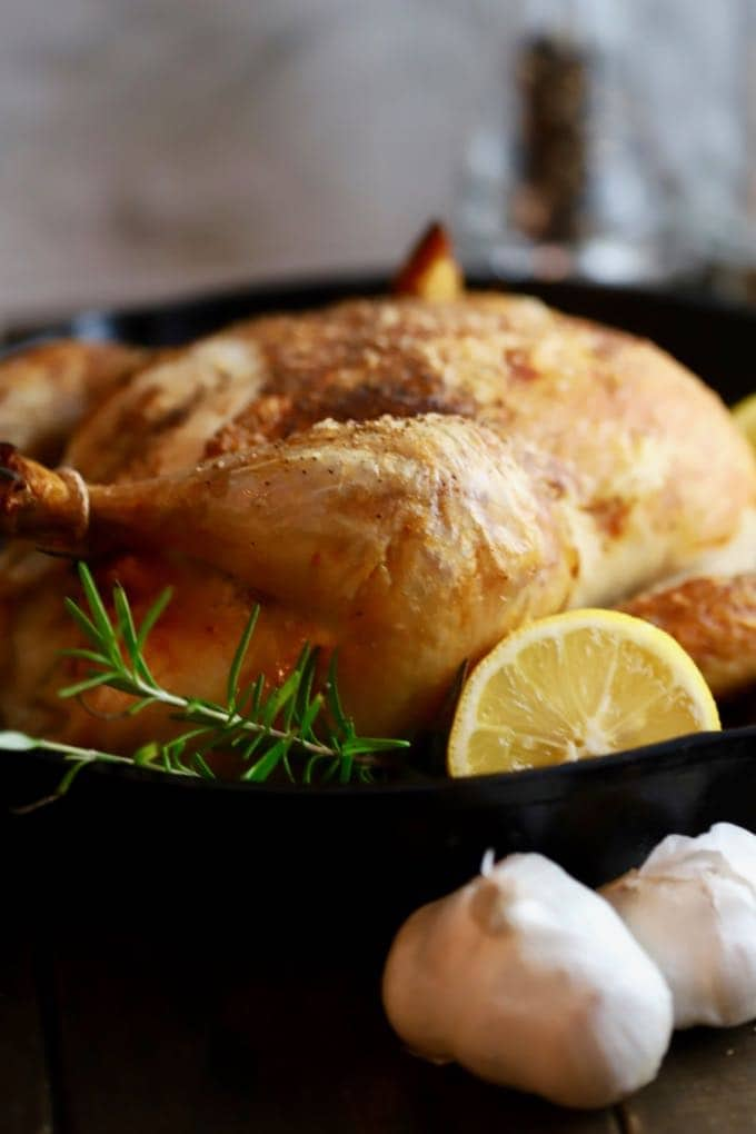 Cast Iron roast chicken in a cast iron skillet garnished with rosemary and lemon.