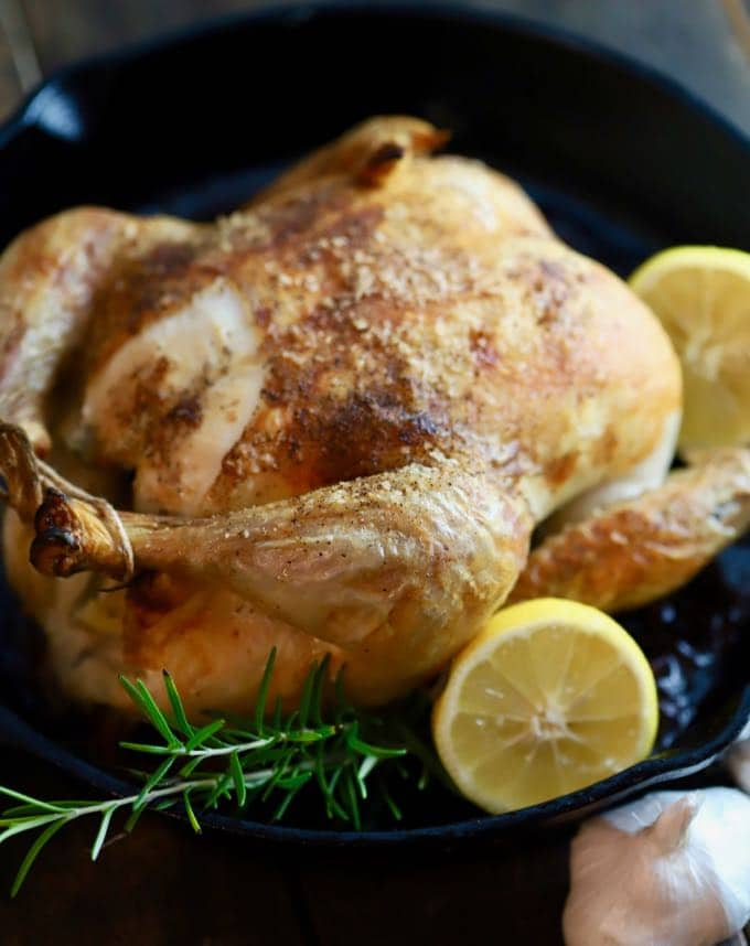 A whole roasted chicken cooked in a cast-iron-skillet and garnished with lemon and rosemary.