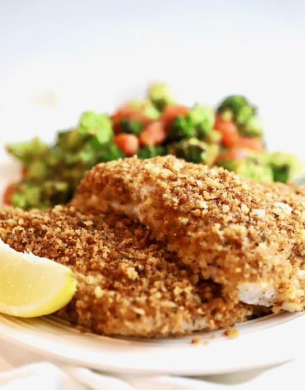 Easy Crispy Oven Baked Grouper fillets on a plate with broccoli and tomatoes