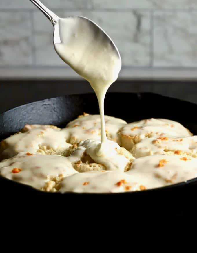 Easy Orange Cinnamon Rolls in a cast iron pan with orange cream cheese glaze being spooned on