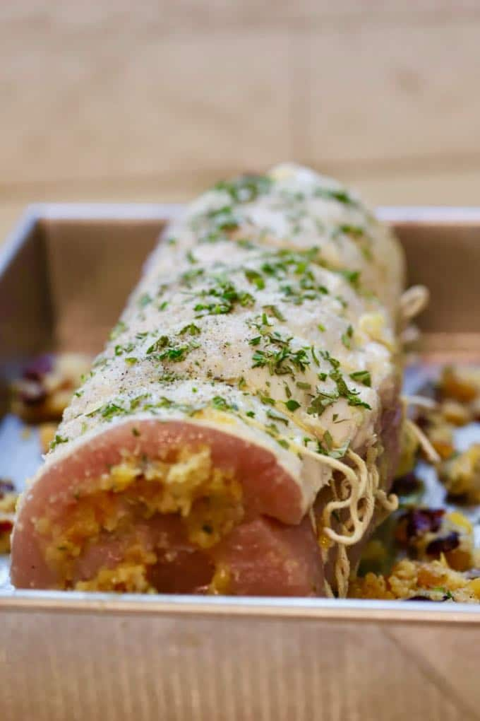 Apricot Cranberry Stuffed Pork Loin Roast covered with fresh herbs ready to bake