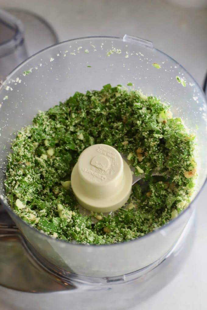 Chopped up basil, cheese, and nuts for Easy Homemade Southern Basil Pesto in a food processor