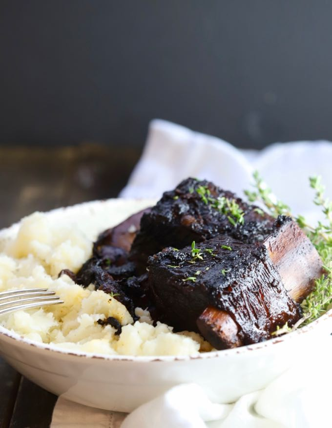 Easy Red Wine Beef Short Ribs in a bowl with mashed potatoes and garnished with sprigs of thyme