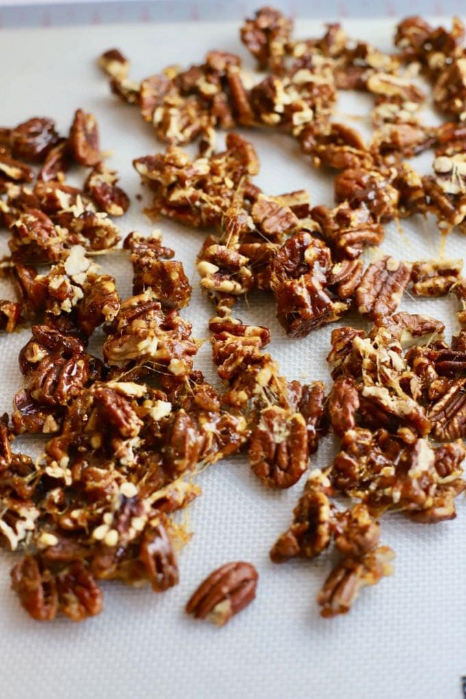Quick and Easy Stovetop Candied Pecans on a silicone mat cooling