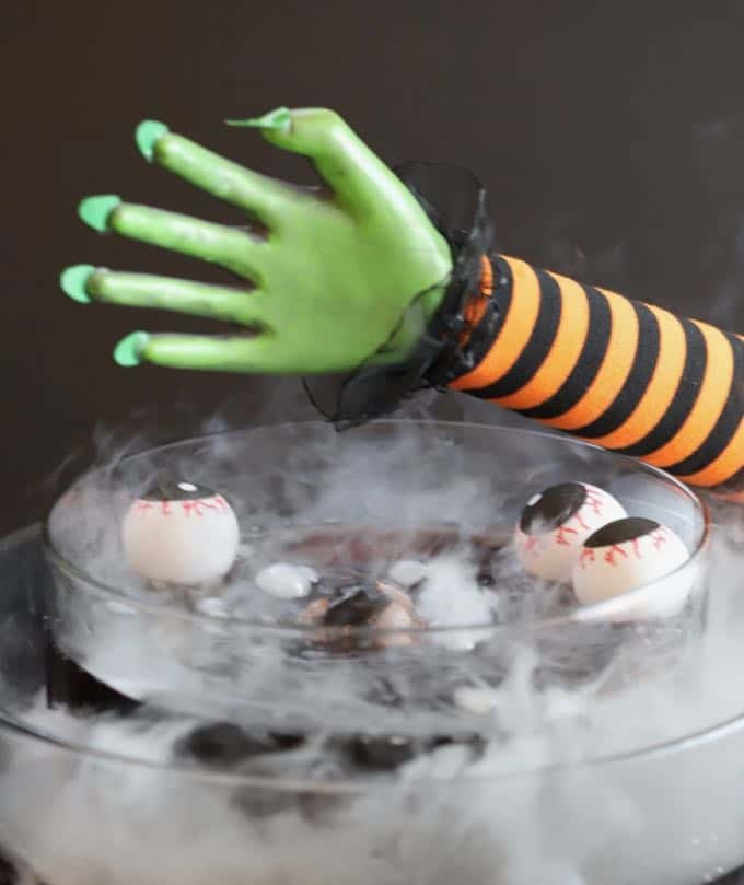 A witches hand over a punch bowl with floating eyeballs for Halloween.