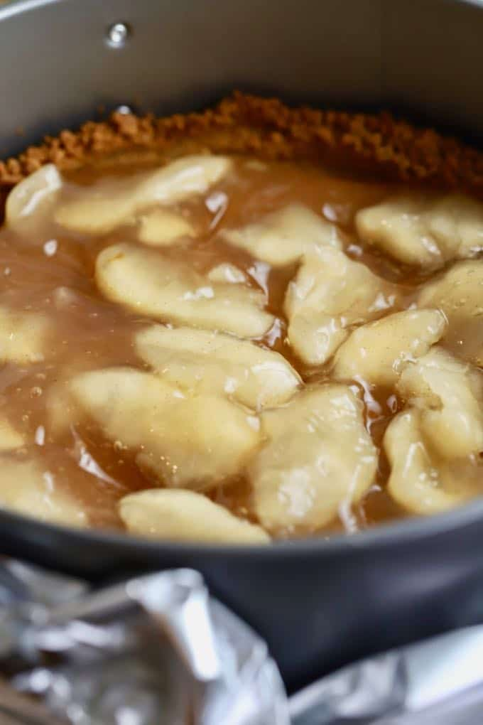Adding apple pie filling to the gingersnap crust for Apple Pie Cheesecake with Caramel Sauce