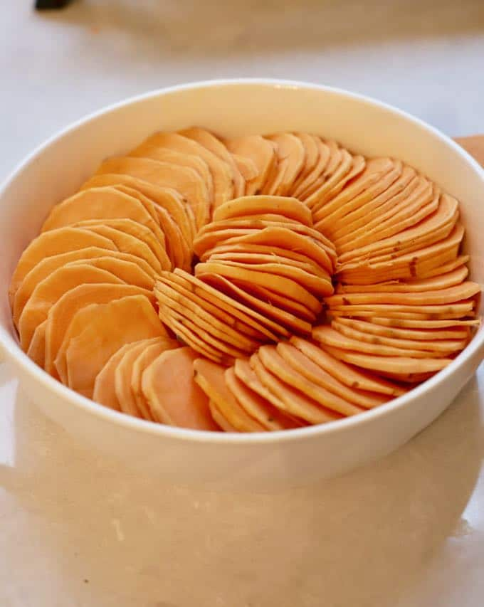 Raw sweet potatoes in a bowl before baking for Baked Southern Candied Sweet Potatoes