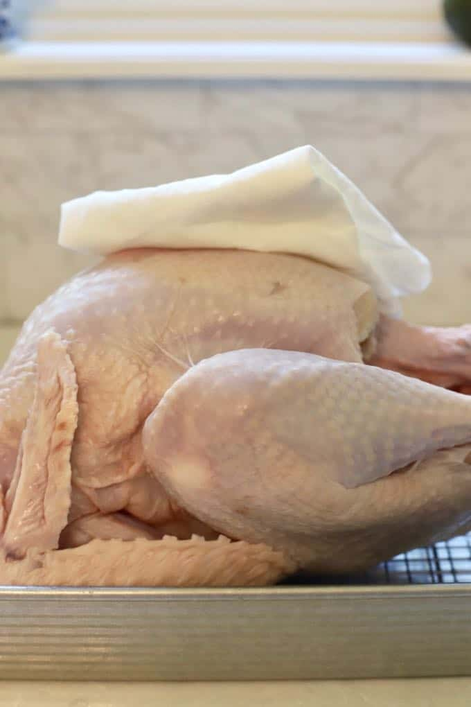 Drying a turkey with a paper towel to make Dry Brined Fried Turkey without Oil