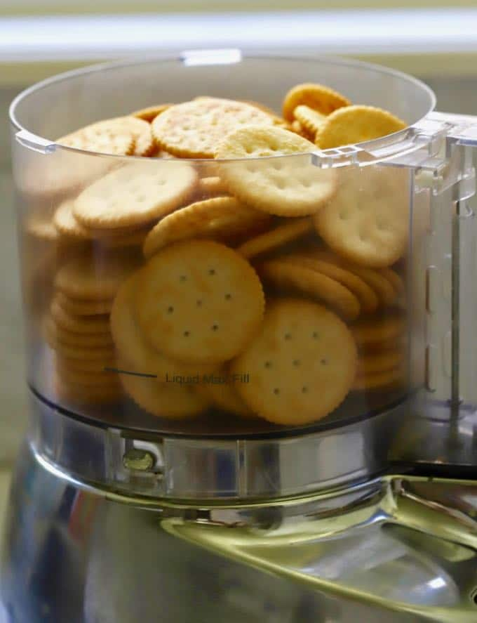 Crackers in the bowl of a food processor for Green Bean Pie with Ritz Cracker Crust