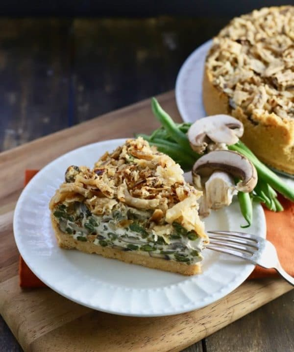A slice of Green Bean Pie with Ritz Cracker Crust garnished with fresh mushrooms and green beans